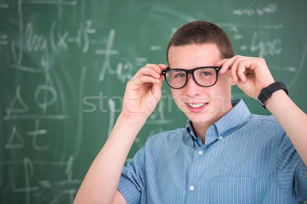 Mosolyog iskolás fiú szemüveg pózol tábla mosoly Stock fotó © zurijeta