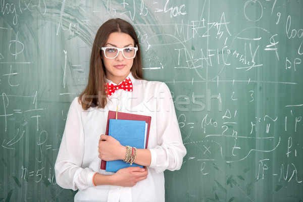 Boldog iskolás lány tart tankönyvek iskolatábla háttér Stock fotó © zurijeta