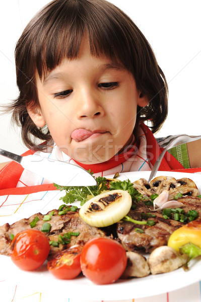 Cute positive boy with fork and knife eating on lunch table Stock photo © zurijeta
