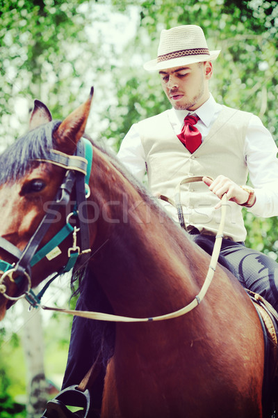 Happy young man on countryside with horse for riding Stock photo © zurijeta