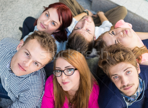Group of young people sitting on floor indoors Stock photo © zurijeta