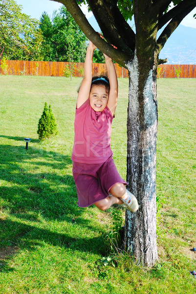 Little cute girl is playing on tree Stock photo © zurijeta