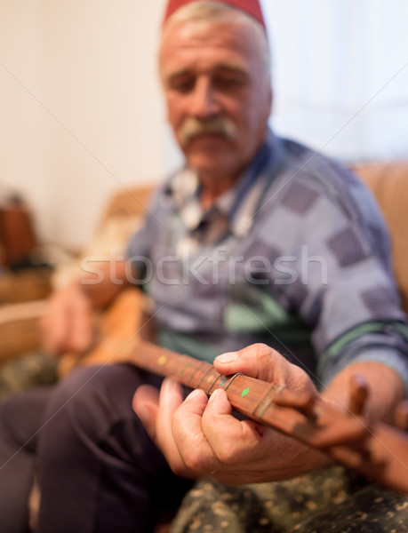 Elderly man with traditional hat playing old type guitar Stock photo © zurijeta