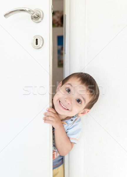 Kid peeking out of the open room door Stock photo © zurijeta