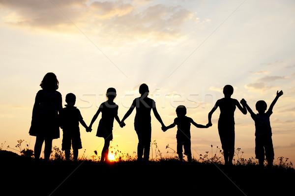 Group of children playing at summer sunset Stock photo © zurijeta