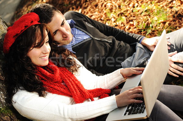 Young couple, male and female sitting in park and studing and workind together with notebook , fall  Stock photo © zurijeta