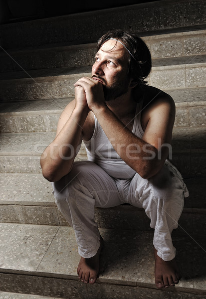 Thoughtful man on black background in low key, sitting on stairs Stock photo © zurijeta