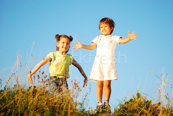 Happy little girl and kid jumping and joying in nature Stock photo © zurijeta