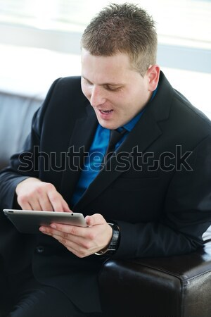 Businessman sitting on leather sofa using tablet Stock photo © zurijeta