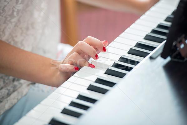 Female hands playing a piano Stock photo © zurijeta
