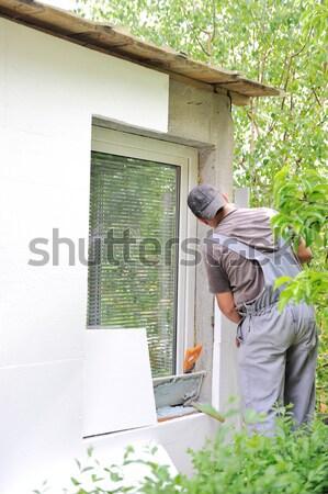 Construction worker applying styrofoam to exterior house wall Stock photo © zurijeta