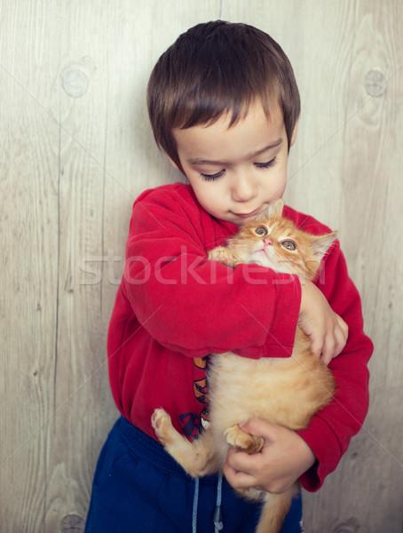 Happy little kid holding yellow kitty cat Stock photo © zurijeta