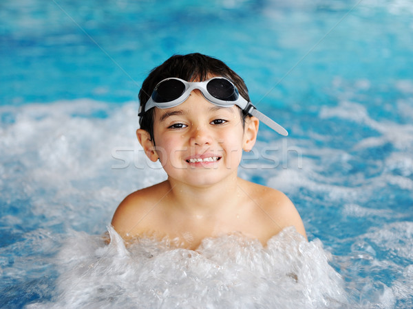 Little cute  boy in blue water of the swimming pool, summer time for fun  Stock photo © zurijeta