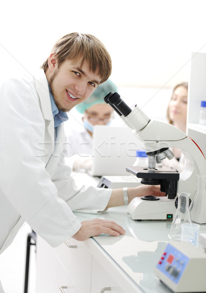 Science team working with microscopes in a laboratory, young researcher smiling Stock photo © zurijeta