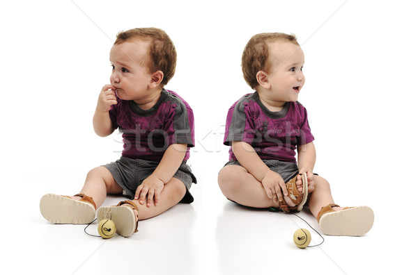 Twin baby boys are sitting together. One baby is angry sad crying and another is happy. Studio shot. Stock photo © zurijeta