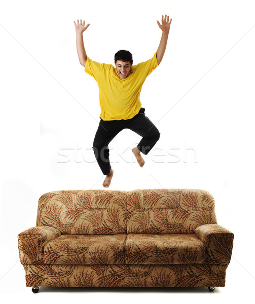 парень прыжки высокий диван изолированный Идея Сток-фото © zurijeta
