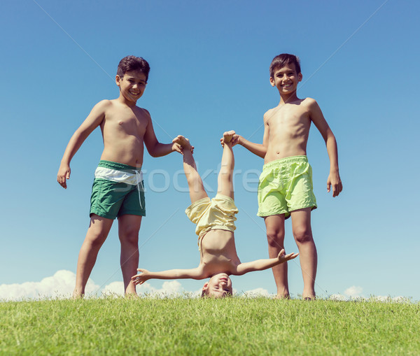 Brothers playing upside down on green meadow Stock photo © zurijeta