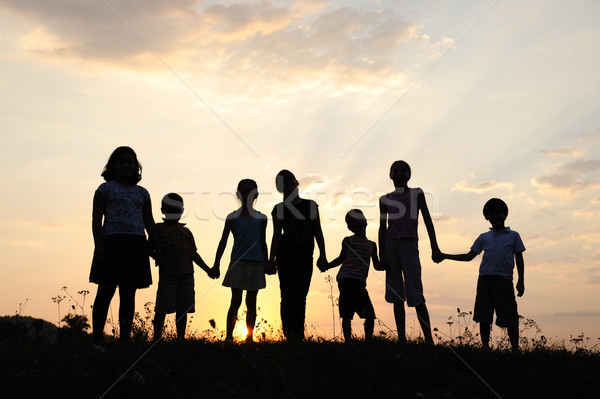 Group of happy children playing on meadow, sunset, summertime Stock photo © zurijeta