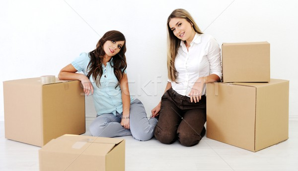 Stock photo: Two beautiful young woman smiling in the room with boxes for mov