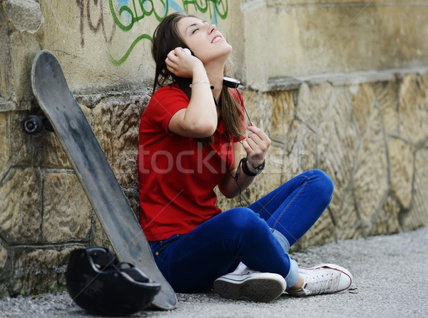 Girl sitting on the street with skateboard Stock photo © zurijeta