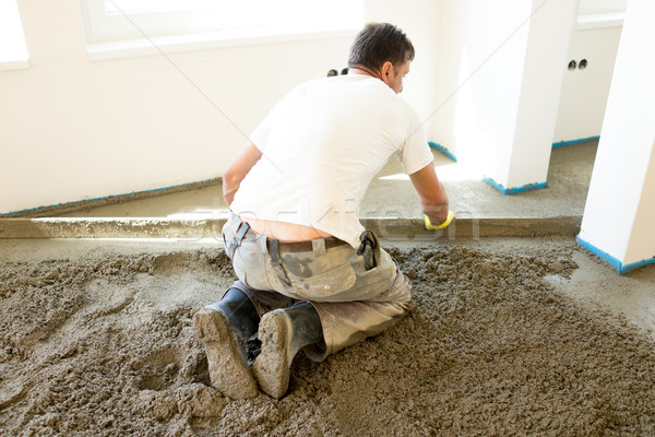 Manual worker leveling estrich plaster Stock photo © zurijeta