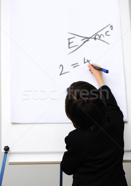Genius little boy writting E=mc2 on the board, new formula instead, conceptual idea Stock photo © zurijeta