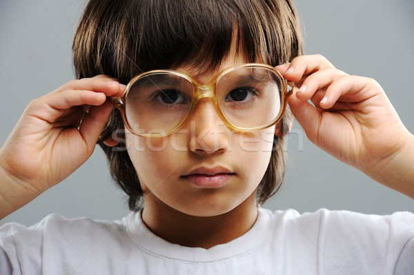 Geeky cute kid studying and wearing glasses Stock photo © zurijeta