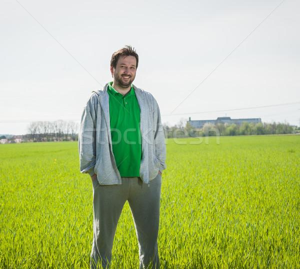 Happy man celebrating success in grass field Stock photo © zurijeta