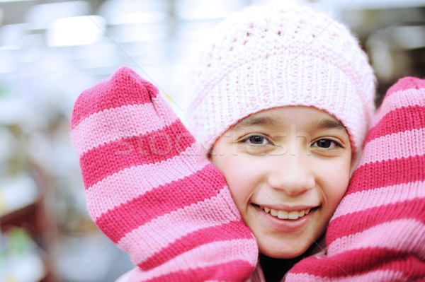 Portrait of a beautiful smiling girl wearing winter hat and gloves Stock photo © zurijeta