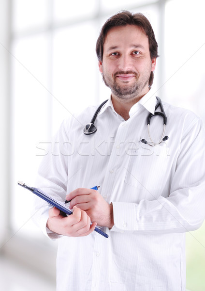 Smiling medical doctor with stethoscope writing a receipt in modern new hospital.  Stock photo © zurijeta