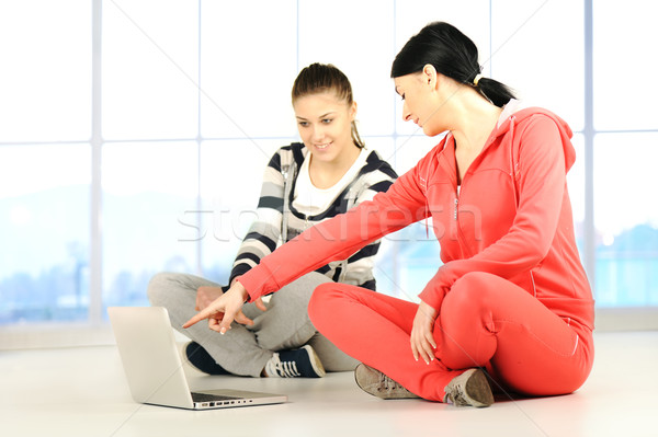 Two girls doing yoga and fitness using laptop in bautiful bright surround  Stock photo © zurijeta