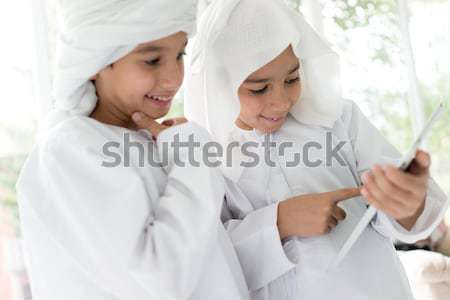 Two Middle eastern brothers together at home using tablet Stock photo © zurijeta