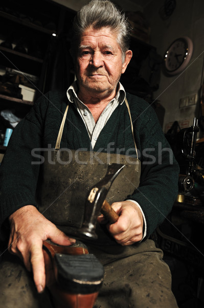 Elderly man, shoemaker repairing old shoe in his workshop Stock photo © zurijeta