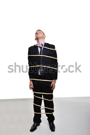 Businessman tied up with a rope looking up Stock photo © zurijeta