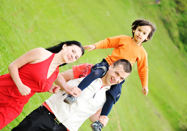 Happy family outdoor, mother father and son, piggy back. Stock photo © zurijeta
