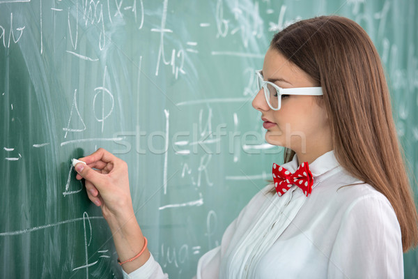 Stock photo: Smart schoolgirl on blackboard