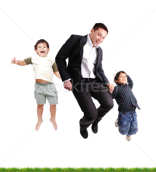 Father and sons  jumping over green grass, isolated Stock photo © zurijeta