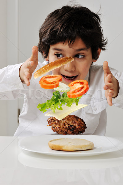 Little boy with hamburger ingredients in hands Stock photo © zurijeta