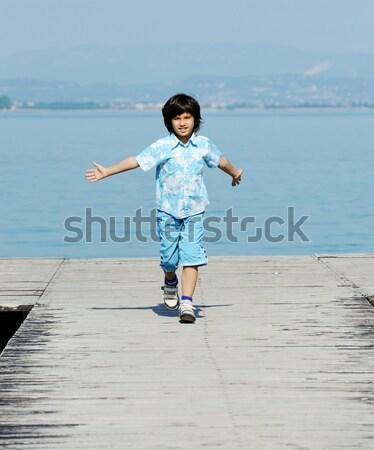 Kid walking and balancing on wall Stock photo © zurijeta