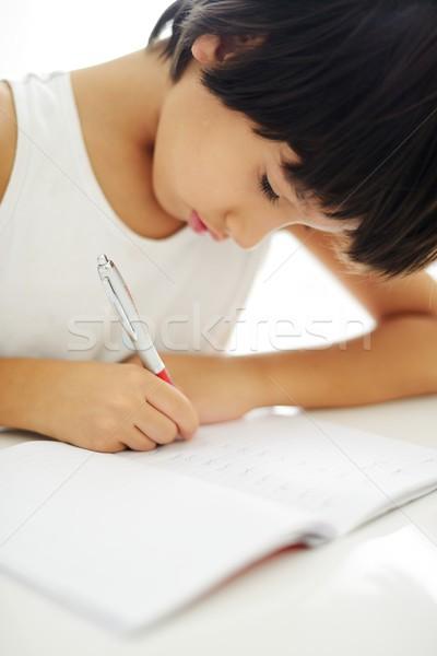 Boy writing on paper at his school Stock photo © zurijeta