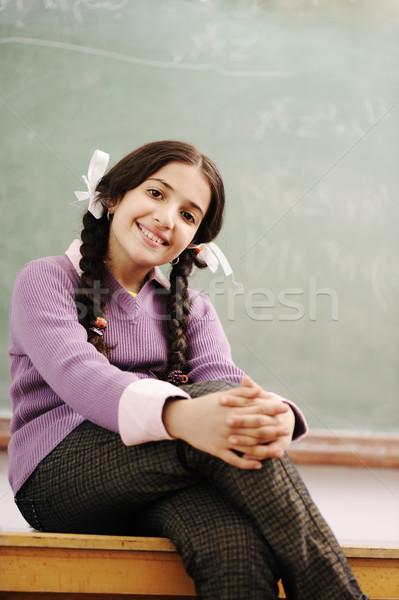 Cute schoolgirl siting on desk in classroom Stock photo © zurijeta