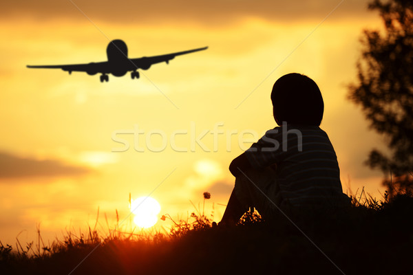 Children play against the sun on summer sunset looking at airpla Stock photo © zurijeta
