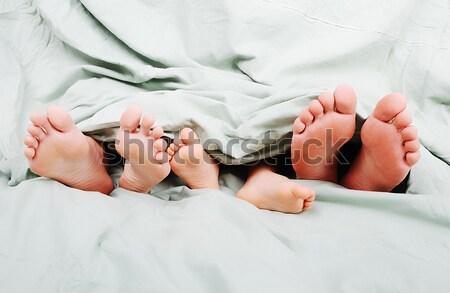 Happy familiy in bed under sheet Stock photo © zurijeta