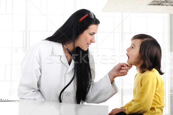 Female doctor examining child with tongue depressor Stock photo © zurijeta