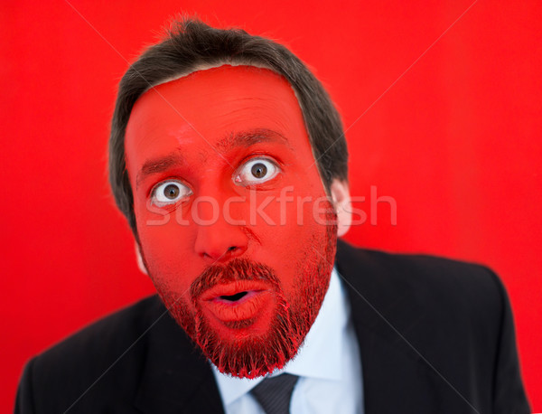 Portrait of surprised adult businessman with colorful red face Stock photo © zurijeta