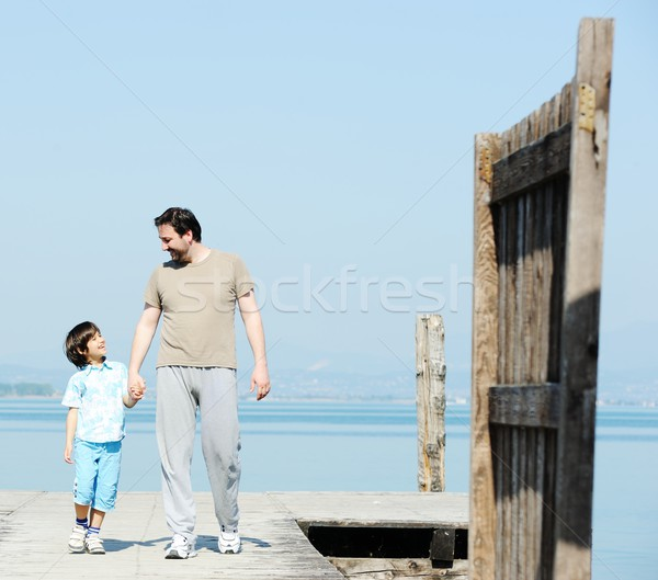 Dad and kid by the dock on a beautiful sea Stock photo © zurijeta