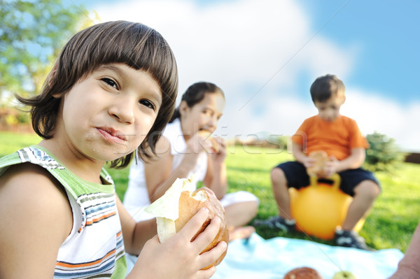 Happy group of children outdoor on meadow: eating and playing together Stock photo © zurijeta