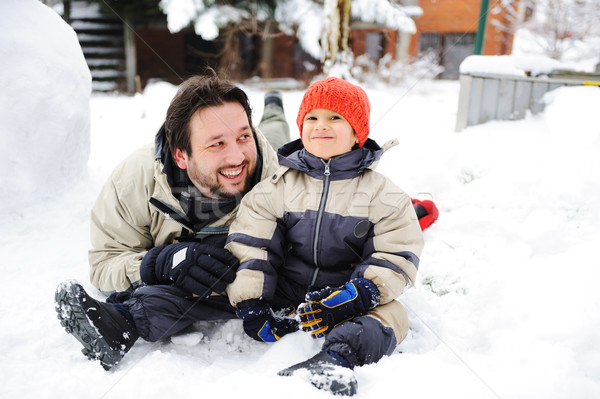 Happy father and cute son together on snow in front of house Stock photo © zurijeta