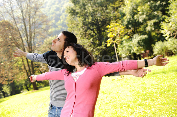 Two young relaxed people in nature with opened arms looking up and breathing fresh air Stock photo © zurijeta