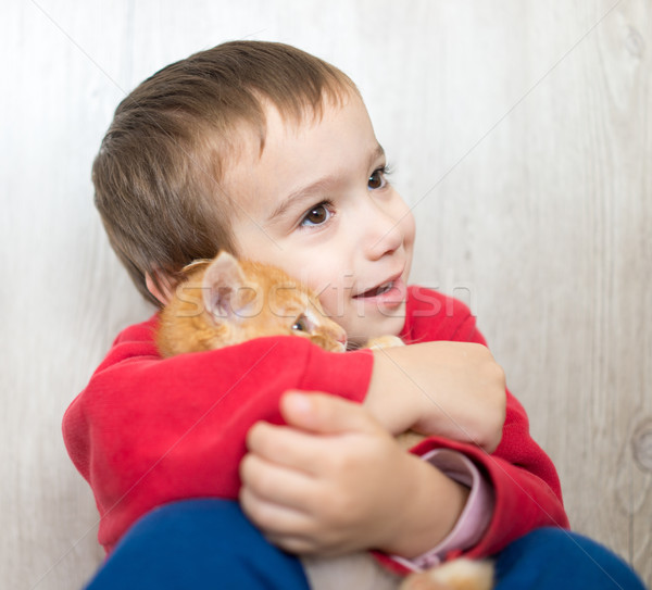 Happy little kid holding yellow kitty cat Stock photo © zurijeta